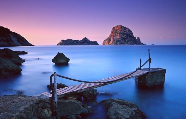 Картинка море, небо, закат, горы, синева, камни, океан, скалы, розовый, берег, Вечер, штиль, деревянный, цепи, мостик, …