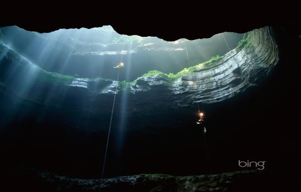 Картинка зелень, свет, скала, темнота, люди, спуск, высота, мох, глубина, луч, фонарь, пещера, новое