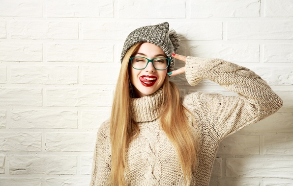 Картинка девушка, стена, шапка, кирпич, макияж, очки, прическа, блондинка, жест, гримаса, свитер
