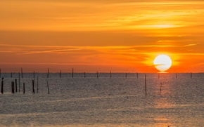 Картинка море, закат, столбы, оранжевое небо