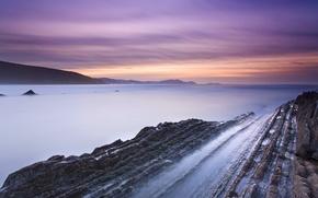Картинка скалы, берег, вечер, залив, Испания, прилив, сиреневое небо, оранжевый закат