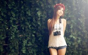 Картинка Азиатка, венок, хвойная стена, фотоаппарат.