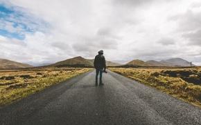 Обои дорога, поле, холмы, джинсы, камера, ботинки, капюшон, мужчина, сельская местность, дождливый