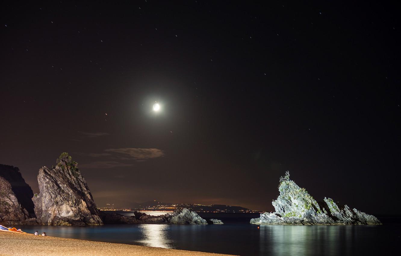 Фото обои море, небо, ночь, город, огни, люди, скалы, берег, Луна