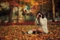 Картинка осень, сидит, желтые, девушка, на земле, брюнетка, боке, листья, деревья, фотографирует, фотоаппарат, парк, съемка