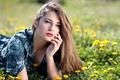Картинка зелень, лето, трава, девушка, солнце, цветы, желтые, макияж, платье, прическа, лежит, шатенка, одуванчики, лужайка, симпатичная, ...